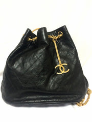 Vintage CHANEL black and beige calf leather hobo bucket shoulder bag with golden CC charm.