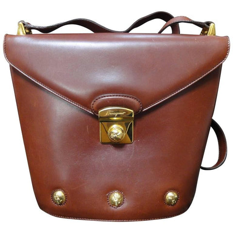 Vintage Salvatore Ferragamo brown leather trapezoidal shape purse with gold tone elegant closure. Ferragamo charms.