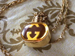 Vintage Gucci gold and brown round shape perfume bottle necklace with iconic logo mark. Perfect rare Gucci gift