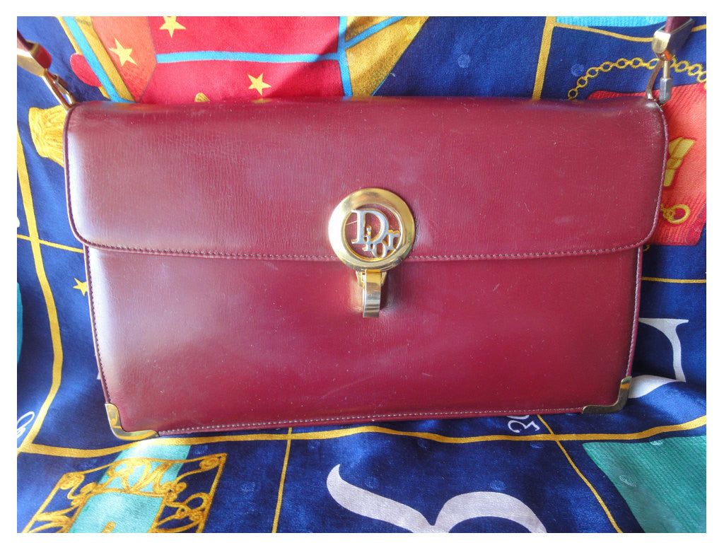 SOLD OUT: Vintage Christian Dior wine leather clutch purse with golden logo motif, detachable strap, and matching coin case.