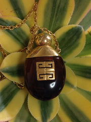 Vintage Givenchy gold chain necklace with gold tone logo motif and brown marble stone perfume bottle pendant top. Statement