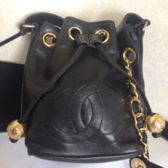 Vintage CHANEL black lamb leather mini hobo bucket drawstring shoulder bag with golden ball charms and CC stitch mark. Classic purse