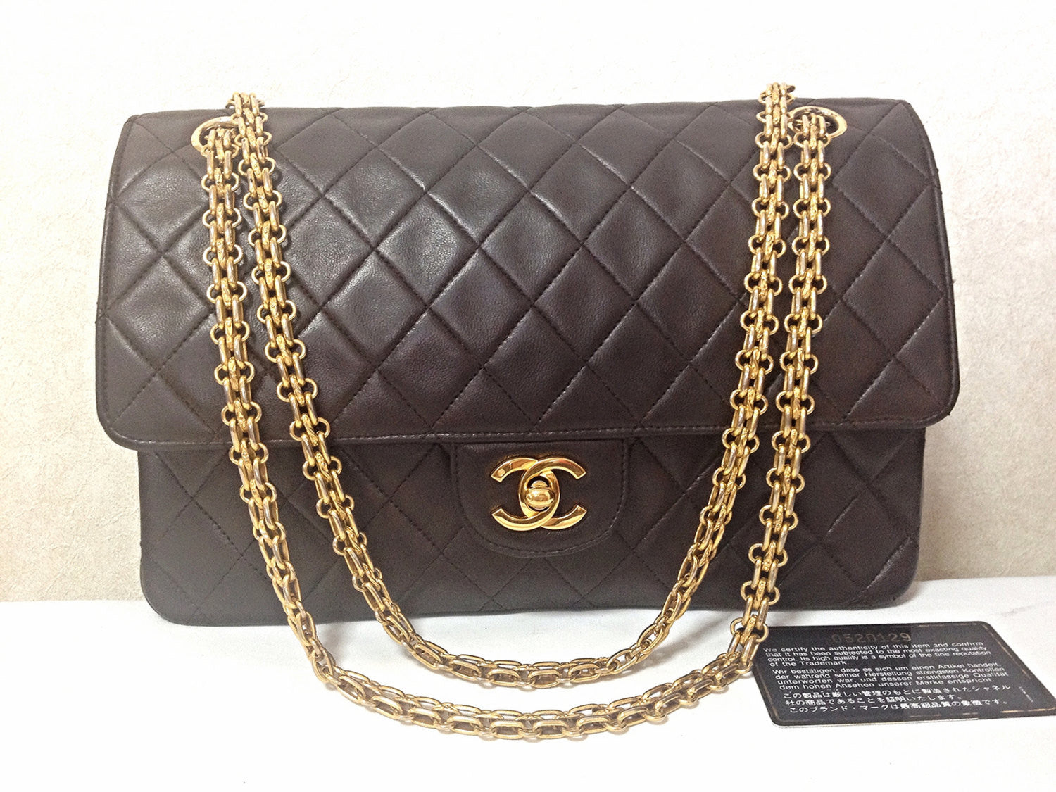SOLD OUT: 80's vintage Chanel dark brown 2.55 classic double flap purse with golden CC motif closure and gold skinny chain straps.