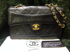 Vintage Chanel classic 2.55 black lambskin shoulder bag with golden chain and unique oval round stitch flap.