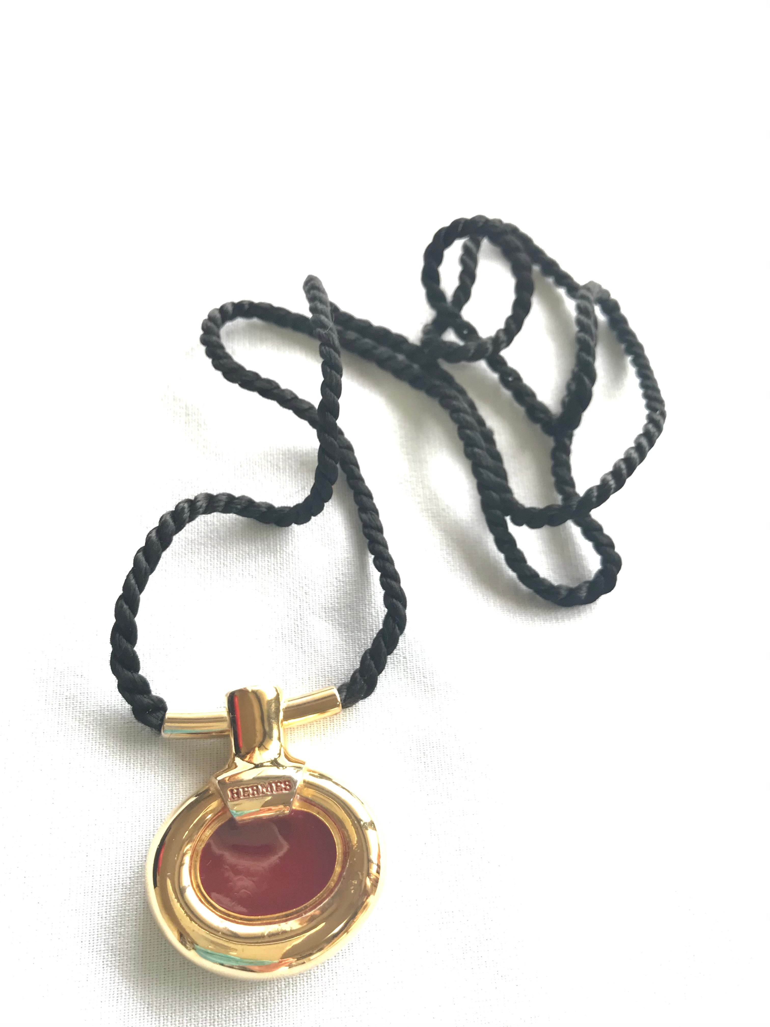 Vintage Hermes golden and red stone charm pendant top necklace with black strings. Unique jewel piece from PARFUM Collection.
