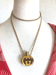 Vintage Gucci gold and brown round shape perfume bottle necklace with iconic logo mark. Rare old Gucci jewelry piece.
