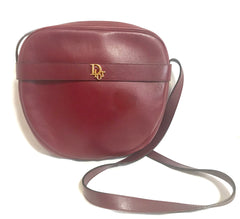 Vintage Christian Dior wine bordeaux leather shoulder bag with golden Dior motif. Round oval purse.