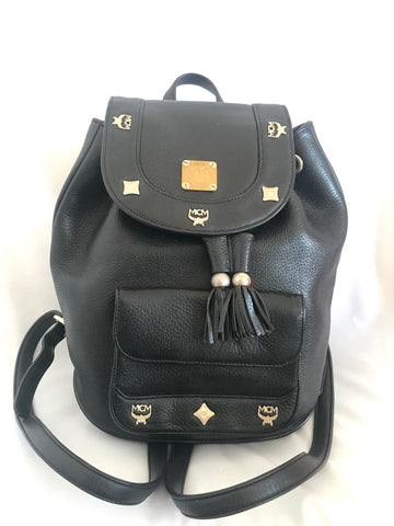Vintage MCM black backpack with golden studded logo motifs and drawstrings. Designed by Michael Cromer. Unisex bag for daily use.