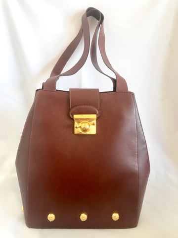 Vintage Salvatore Ferragamo brown leather bag with gold tone elegant closure. Featuring Ferragamo charms.