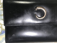 Vintage Cartier black leather wallet with silver tone kiss lock closure. Panthere collection. Unisex use.