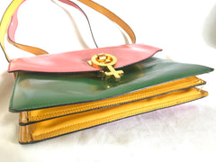 Vintage MOSCHINO pink, green, and yellow patent enamel leather shoulder bag with golden men symbol motif at closure. Masterpiece by Red wall