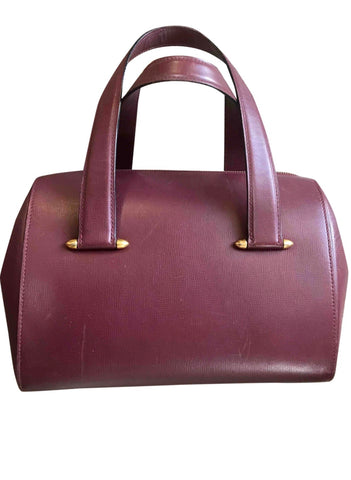 Vintage Cartier classic wine, bordeaux leather handbag purse in unique shape with bullet design gold hardware at handles. Must de Cartier
