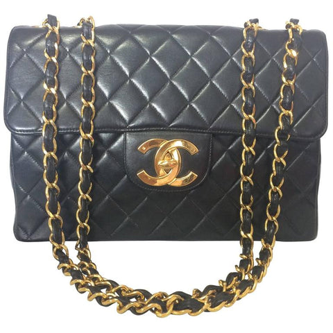 Vintage CHANEL black lamb leather large, jumbo shoulder bag with a big golden CC closure and chain strap. 2.55 classic purse