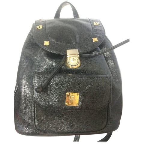 80's vintage MCM genuine leather black backpack with golden studded logo motifs. Designed by Michael Cromer. Unisex bag for daily use.