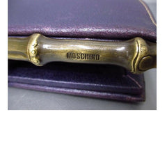 Vintage MOSCHINO purple pigskin oval shape clutch bag with bamboo style kiss lock closure. Masterpiece produced by Red Wall