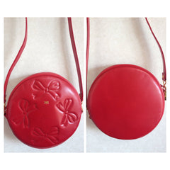 SOLD OUT: Vintage Nina Ricci red leather round shoulder bag with golden bow, ribbon shape logo motif and stitch marks. Perfect daily purse