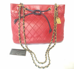 Vintage CHANEL classic tote bag in red leather with gold tone chain and navy blue leather straps and logo CC charm plate. Rare bag