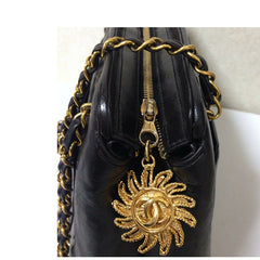 Vintage CHANEL black lambskin chain shoulder bag in vertical quilting stitch with the gold tone sun flower motif CC charm. Classic bag
