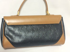 Vintage Yves Saint Laurent YSL logo embossed black leather handbag purse with brown leather trimmings and golden charm.