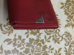 Vintage Yves Saint Laurent red leather wallet with YSL logo embossed motif at front.