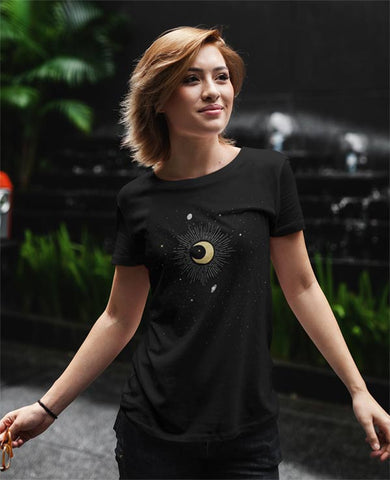 Image shows a young woman wearing a soft black Bella & Canvas T-Shirt features an illustration of the crescent moon in the center, surrounded by stars, Jupiter, Saturn, Mercury and Pluto. The constellation is Capricorn.