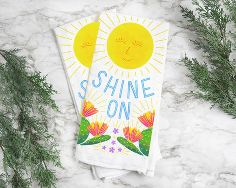 "tea towel with colorful illustrated cheerful sunshine with hand lettered ""Shine On"""