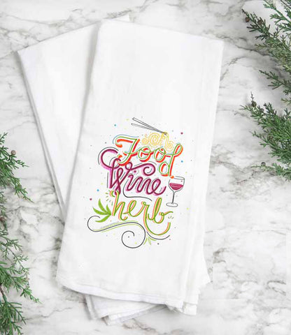 "White cotton tea towel features hand illustrated and lettered ""Food, Wine, Herb"" with illustrated elements."