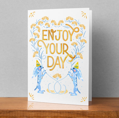 "5 X 7 folded greeting card with ""Enjoy Your Day"" hand lettered between two festive blue jack rabbits wearing party hats. Great for birthdays and all days."