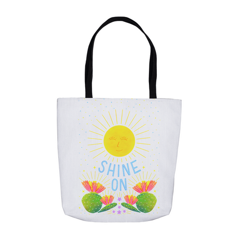 "Durable white tote printed with hand lettered ""Shine On"" phrase within illustration of a sunshine and prickly pear cactus. Perfect for Farmers Markets and beach days."
