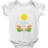 "white short sleeved Rabbit Skins onesie with illustrated sunshine and flowers; hand lettered ""Shine On"" is written in the design."