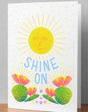 "5x7 folded greeting card with an illustrated sunshine and cactus flowers, that reads, ""Shine On"" in hand lettered text. Illustrated by Alesha Sevy Kelley."