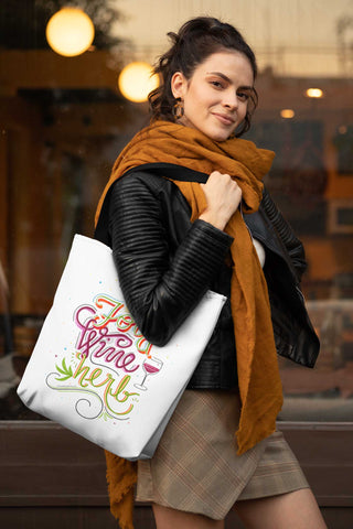"Image features a young woman carrying a white tote with a black handle. The tote is hand lettered and illustrated with the phrase ""Food. Wine. Herb."" and features illustrated noodles, a glass of wine and a cannabis leaf."