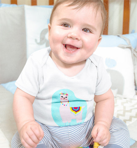 Cute smiling baby wearing white short sleeved Rabbit Skins onesie with a hand illustrated pink llama on a light cerulean aqua blue starry background.