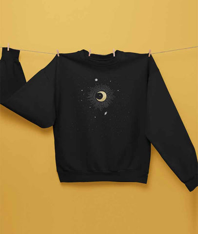 Black sweatshirt features an illustration of the crescent moon in the center, surrounded by stars, Jupiter, Saturn, Mercury and Pluto. The constellation is Capricorn.