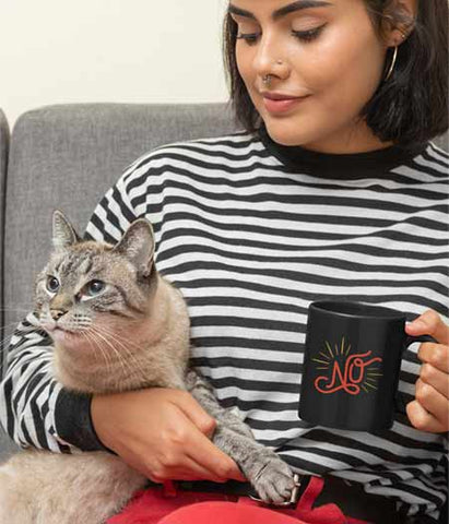 "Woman holding a cat holding a hand lettered, illustrated mug that reads, ""NO"" in red lettering with yellow sun rays."