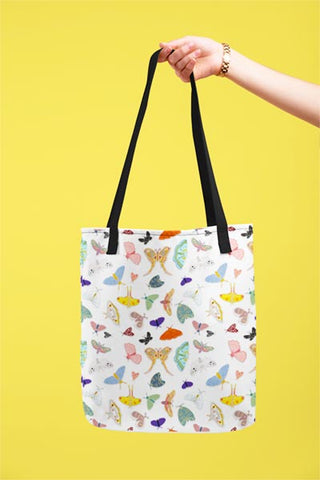 sturdy white tote with black handle features hand illustrated moths in a variety of colors and patterns.