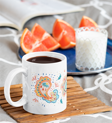 White coffee mug featuring digital illustrations of intricate paisley patterns.