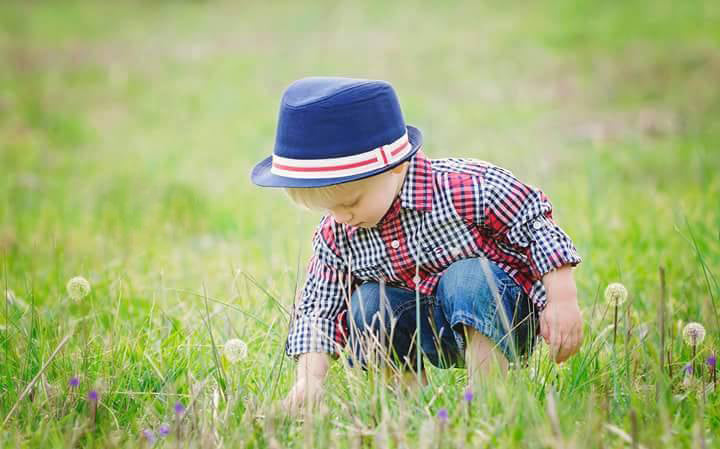 photo of a young boy squating in a field of wild grasses