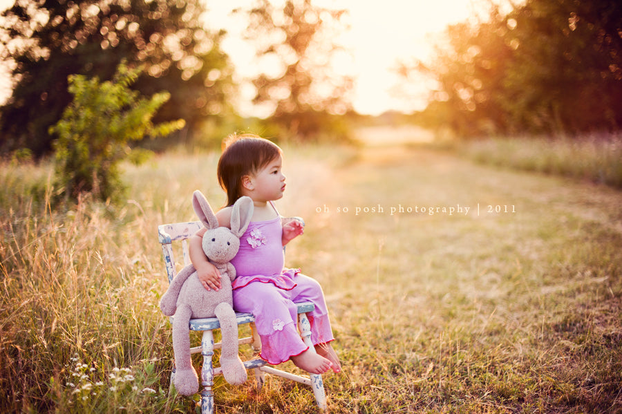 Backlit photo of girl sitting on a chair with her bunny