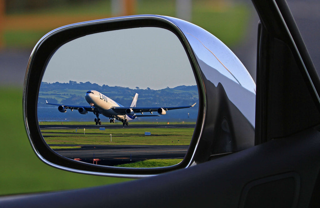Perspective Photo of a Plane from the Perspective of a Rear View Mirror