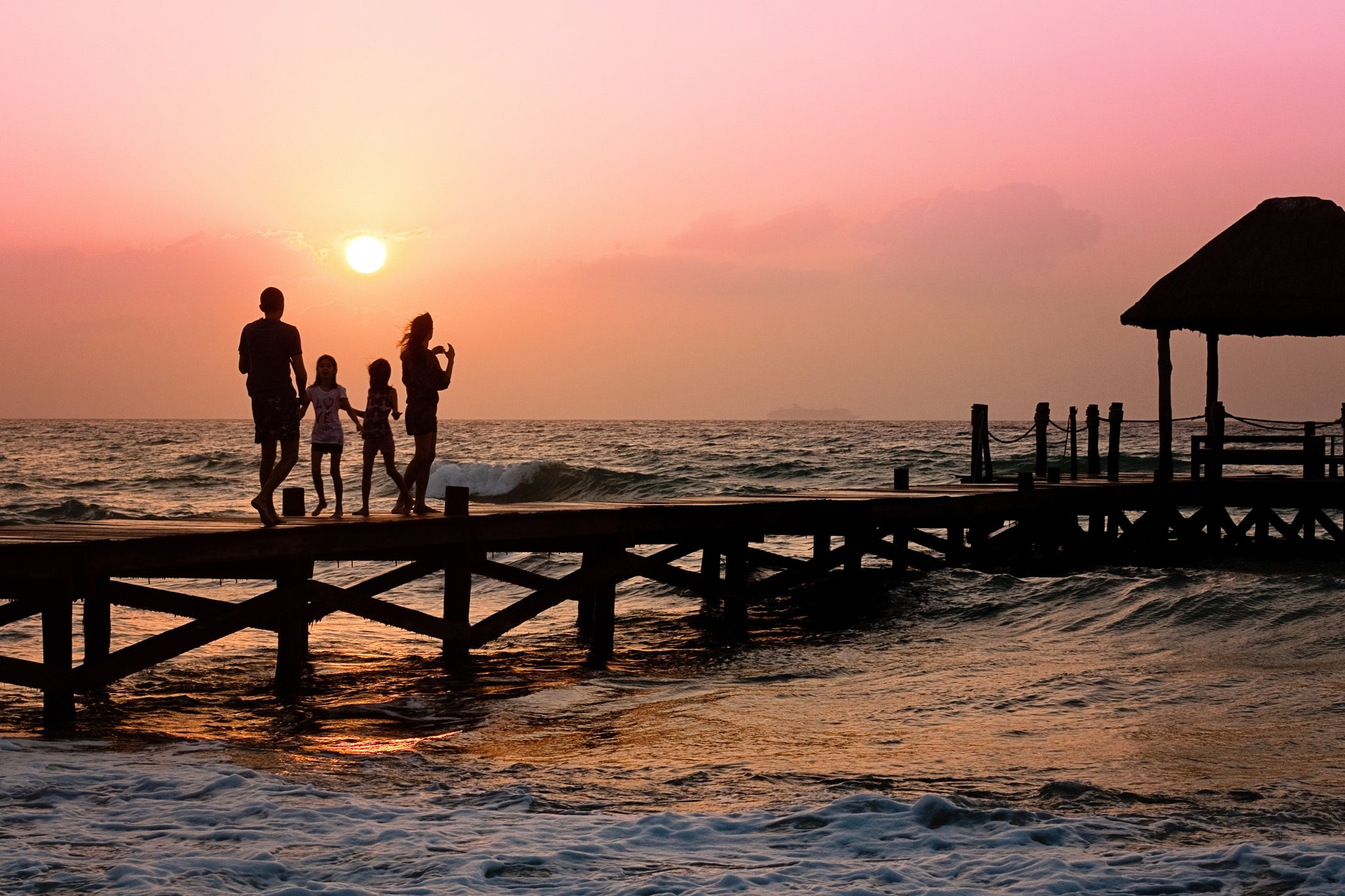 photographing silhouette of a family on a pier at sunset