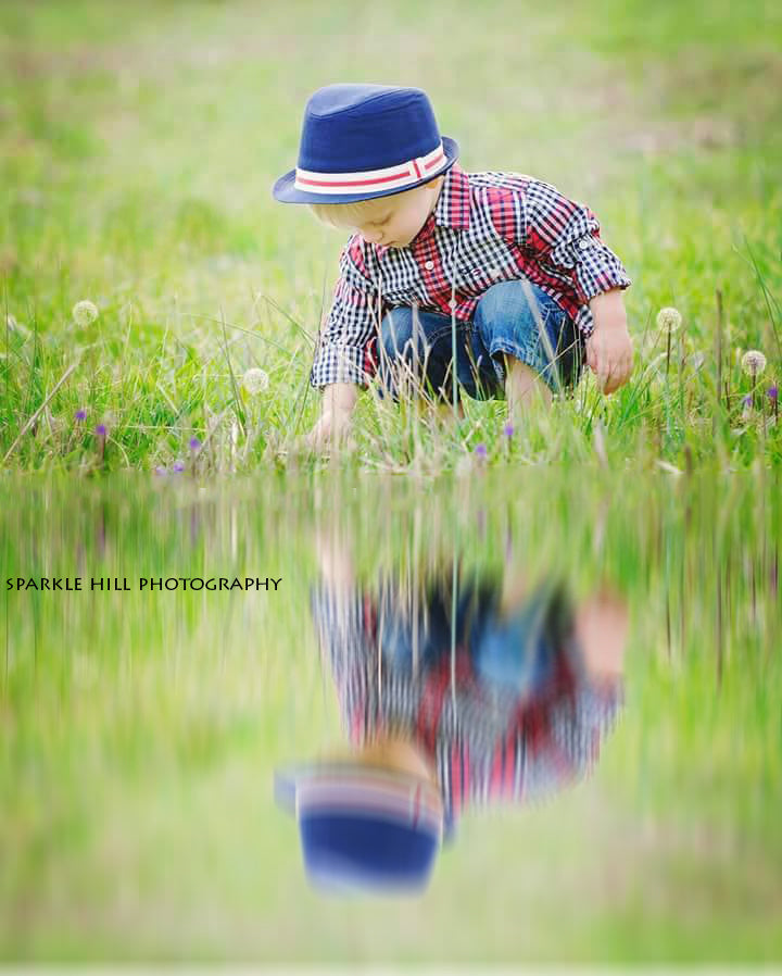 young boy looking at his reflection in a pond