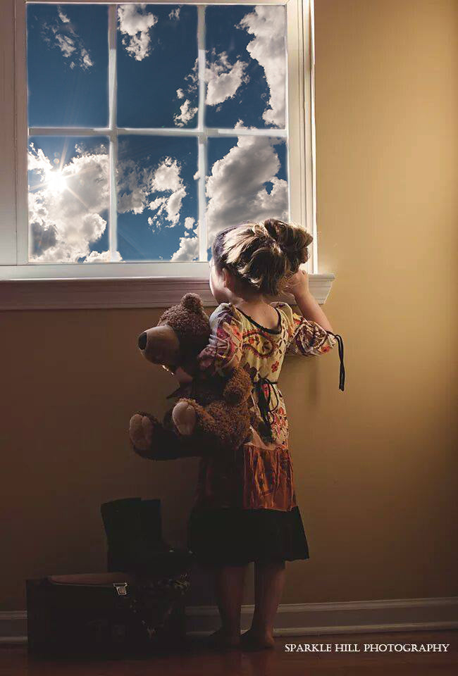 girl with teddy bear looking out the window with cloud overlay