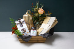 Gourmet gift basket with salted caramels, fig jam, hand woven linen napkins, mercury glass pumpkin, and bud vase of fresh fall flowers.