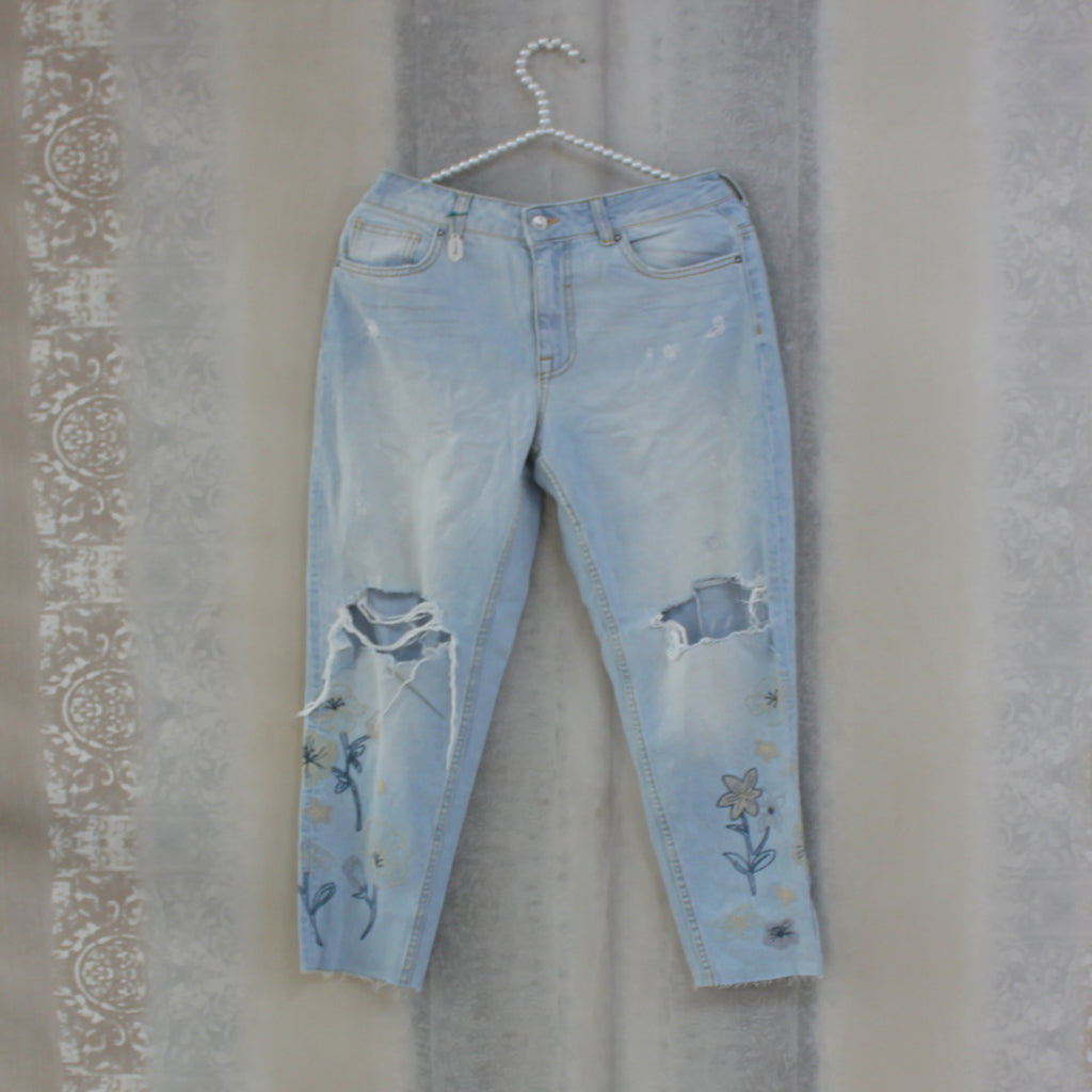 Faded blue destroyed denim jeans