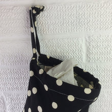 Load image into Gallery viewer, Plastic bag storage dispenser with large spots on a black background with drawstring top
