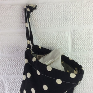 Plastic bag storage dispenser with large spots on a black background with drawstring top