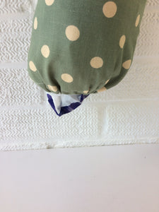 Green with large spots plastic bag dispenser with a draw string and elastic bottom