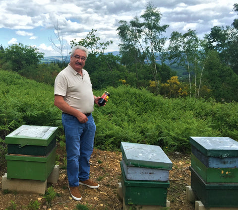 David Raw Honey Beekeeper with Hives and Honey