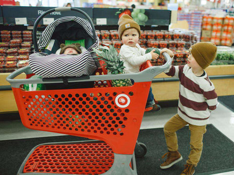 kid pushing cart with baby in grocery cart hammock and car seat